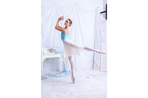Professional ballet dancer posing on white