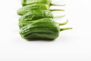 Close-up of green peppers placed in line on white background. Healthy food.