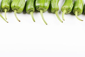 Close-up of green peppers placed in line on white background. Isolated. Healthy food.