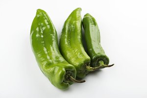 Close-up of three green peppers on white background. Isolated.