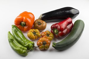 Appetizing tomatoes, red pepper, aubergine and gherkin on white background. Isolated.