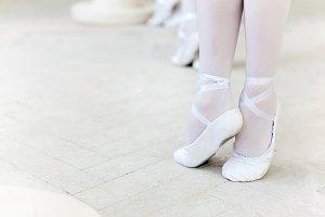 Three little ballerinas dancing. legs in ballet flats close-up