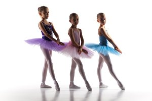 Three little ballerinas dancing in dance studio