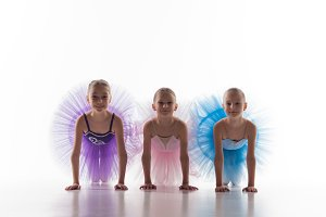 Three little ballet girls sitting in tutu and posing together