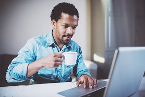 Smiling attractive African man making video conversation via laptop with partners while drinking white cup black tea in meeting office.Concept of happy business people.Blurred background,film effect.