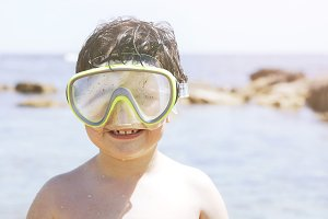 Boy with diving goggles on the beach