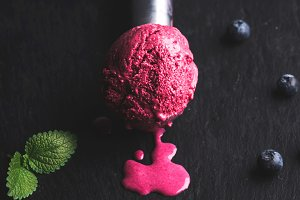 Melting blueberry ice-cream scoop