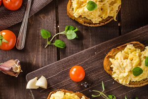 Scrambled eggs with herbs and garlic on toasted bread