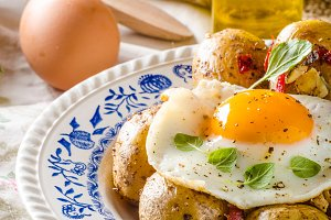Baked potato with chili and fried egg