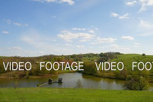 clouds timelapse of lake with water houses in spring fields and forest landscape