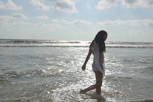 Young woman in bikini and shirt walking at the ocean water on beach. Beautiful girl enjoying life and having fun at sea shore. Summer vacation or holiday
