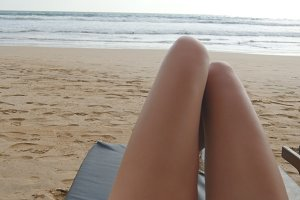 Point of view of young woman lying on sunbed by the sea and tanning. Female legs on chaise-longue relaxing and enjoying during summer vacation on ocean beach. Foot of girl on a resort. Close up Pov