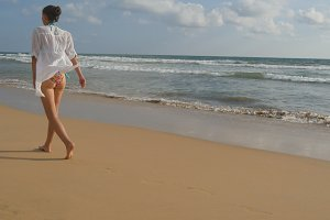 Beautiful woman in swimsuit and shirt walking on sea beach barefoot. Young girl going on the ocean shore. Female foot stepping on the sand with sea waves background. Summer vacation concept Rear view