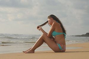 Beautiful young woman in bikini sitting on golden sand on sea beach. Tanned girl relaxing on perfect paradise shore during summer vacation travel. Ocean waves at background. Close up