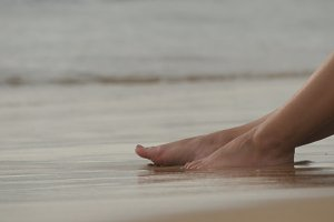Beautiful young woman lying on golden sand on sea beach and relaxing during summer vacation travel. Sexy female body. Close up