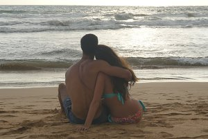 Young romantic couple is enjoying beautiful view sitting on the beach and hugging. A woman and a man sits together in the sand on the seashore, admiring the ocean and landscapes.Close Up