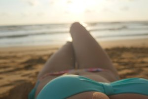 Point of view of sexy girl lying and tanning on the beach. Beautiful young woman relaxing on sea shore during summer vacation travel. Female body sunbathes against the sea. Relax summer vacation. Pov