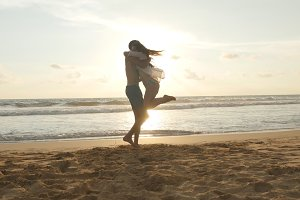 Young couple is running on the beach, man hug and spin around his woman on sunset. Girl jumps into her boyfriend arms, he whirling her at beautiful seaside. Having fun together at vacation. Close up