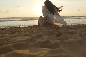 Beautiful young woman sitting on golden sand on sea beach during sunset and calls to himself. Girl relaxing on ocean shore during summer vacation travel at sundown. Ocean waves at background. Close up