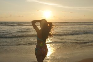 Attractive sexy girl with long hair posing on the ocean shore at sunrise. Beautiful young woman in bikini standing in the sea on sunset. Female on the beach enjoying life during vacation. Close up