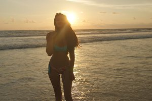 Attractive sexy girl with long hair seduces and posing on the ocean shore at sunrise. Beautiful young woman in bikini calling with herself near the sea on sunset. Female on the beach enjoying life
