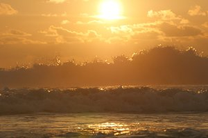 Beautiful golden ocean waves on sunset. Orange sunrise reflected at the sea water. Strong tide with waves splashes on a windy day at evening. Nature background Close up