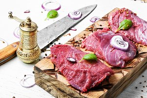Raw meat on wooden cutting board