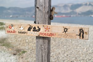 Wooden signboard in Russian on the background of the sea: May, Peace, Work, Victory, Love
