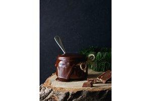 Homemade dark hot chocolate in a glass jar. Dark background with winter decoration of spruce .
