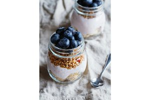 Close up of granola with fresh berries, raspberry yogurt and banana in glass jars on a rustic flax beige napkin