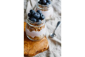 Close up of granola with fresh berries, raspberry yogurt and banana in glass jars on a rustic wooden board and flax beige napkin