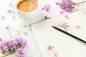 Coffee mug, flowers and notepad