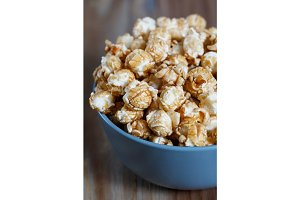 Blue bowl with caramelized popcorn on a wooden table.