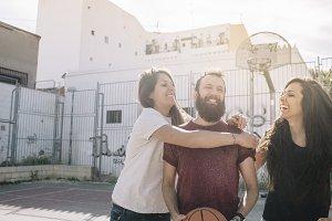 Three friends playing basketball