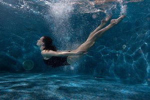 Woman floats under water in the pool.