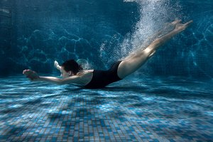 Woman quickly swims under the water.