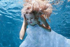 Woman in white dress under water pool.