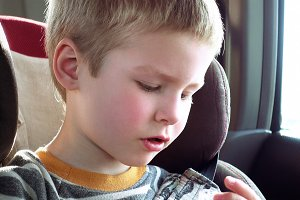 Cute boy in a child car seat plays with a toy