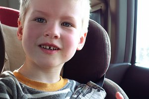 Cute boy in a child car seat smiles and laughs