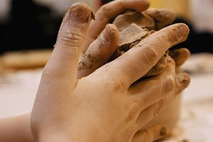 Sculptor is pugging clay for creating pottery