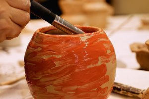 Ceramist is painting clay pot or vase bowl