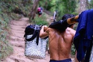 Sherpas man carry on a shoulder pole