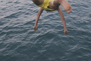 boy jumping into the water