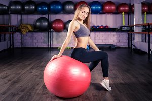 Young beautiful fitness girl sitting on red ball
