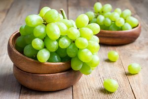 Bunch of green ripe grapes in a wooden bowl