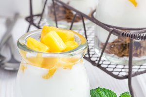 Breakfast dessert with bran flakes, plain yogurt and mango, closeup