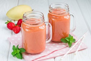 Healthy smoothie with strawberry, mango and banana in glass jars