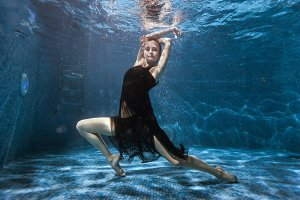 At the bottom pool, a woman dances under water.