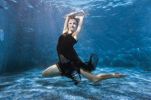 Woman dances under the water in the pool.