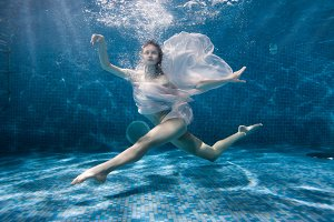 Woman is dancing underwater sports dance.
